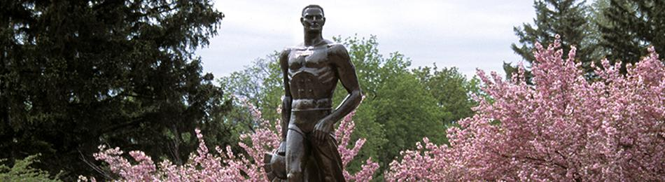 Photo of MSU Sparty in the spring; a bronze sculpture with flowering trees behind it.